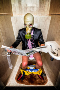 Man in suit wearing gas mask reading newspaper on the toilet