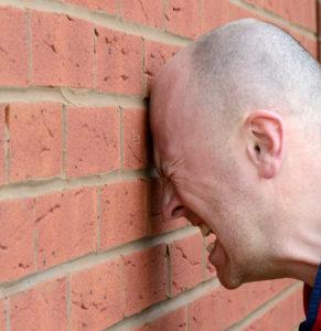 Man banging head against wall