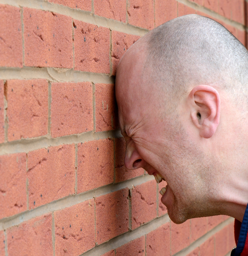 Man banging head against wall