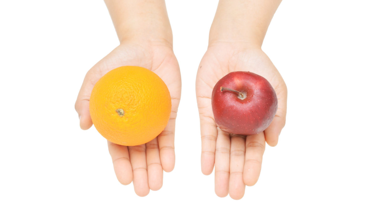 person holding an apple in one hand, orange in another