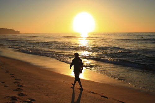 photo of man walking on beach at sunrise