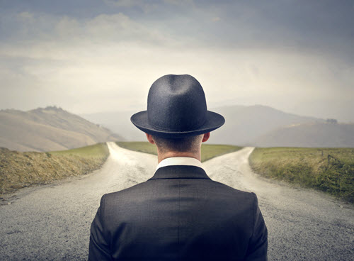 man-in-suit-hat-standing-at-fork-in-road