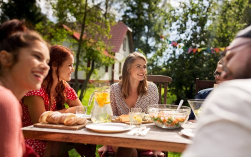 Woman smiling with friends outside at picnic table meal
